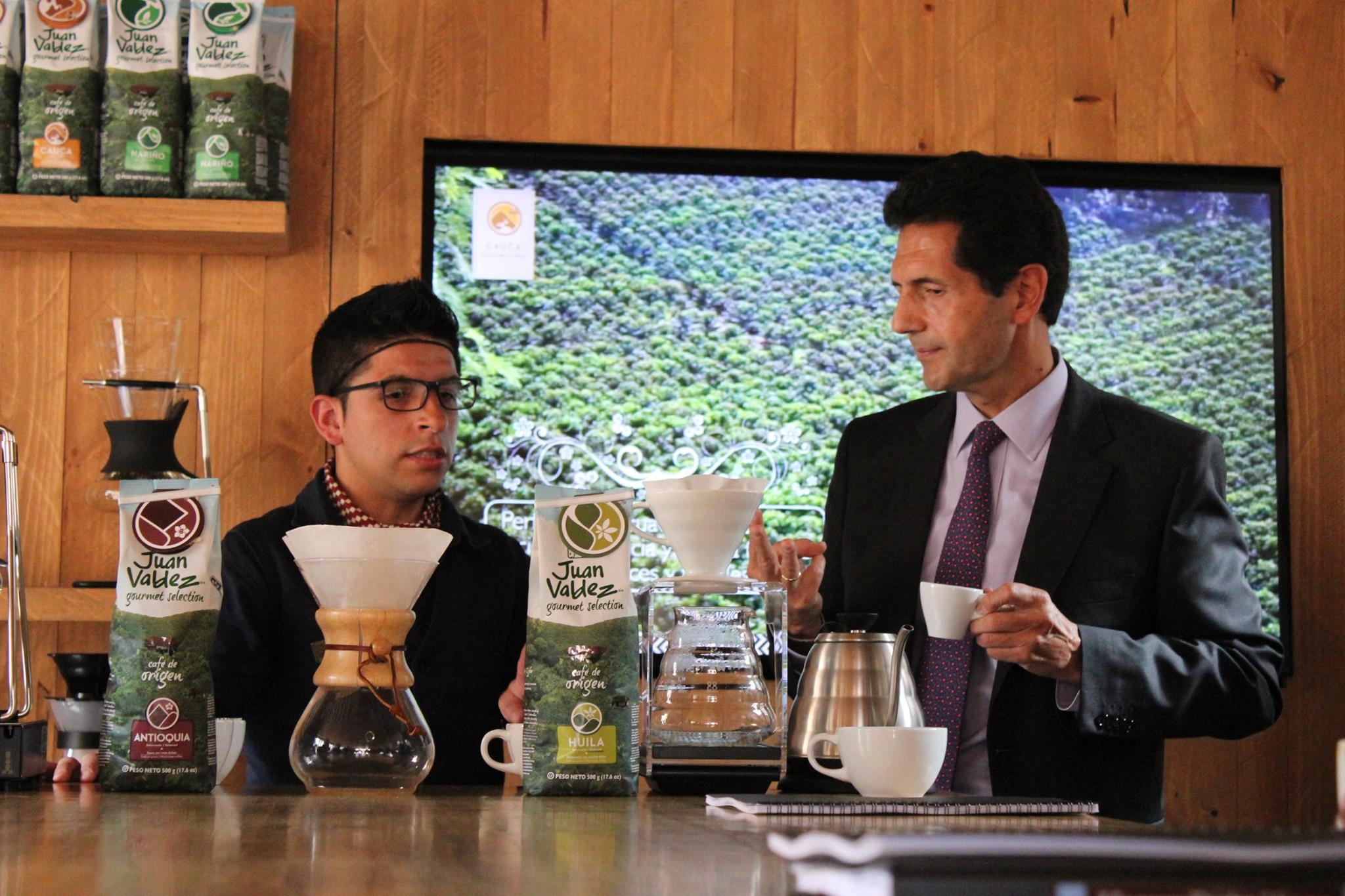 Procafecol President Hernan Mendez with Baricultore in Mug of Coffee at Juan Valdez Cafe in Bogota, Colombia