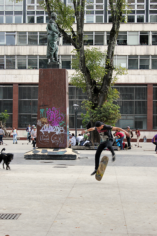 Skateboarder Attempts Kickflip Parque Santander Plaza en Bogotaá, Colombia