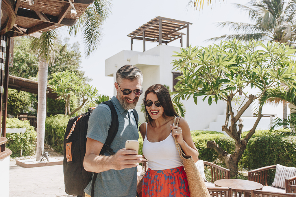 Couple Using Mobile Travel App on Cell Phone