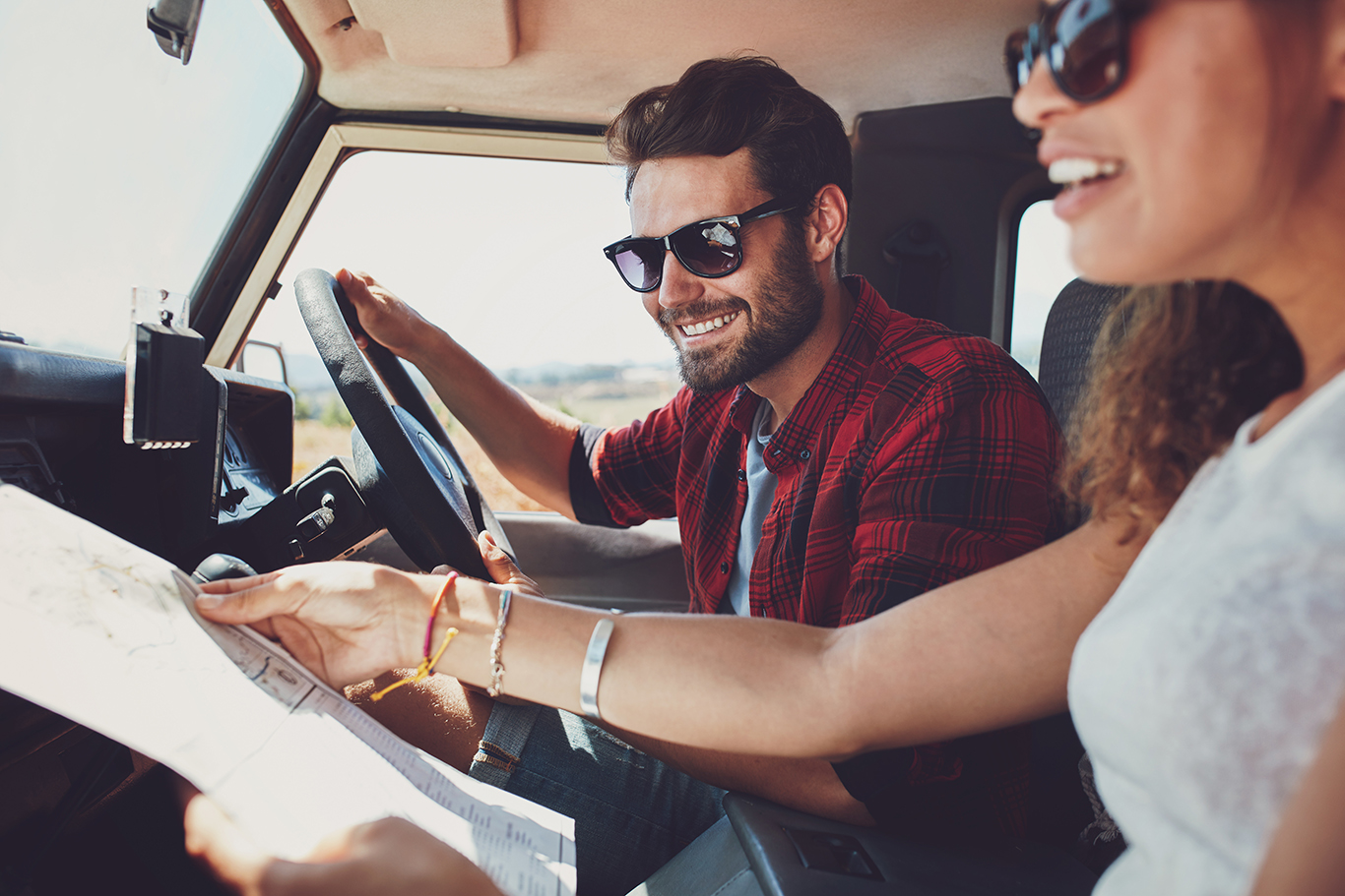 Couple Planning Road Trip with Map in Rental Car